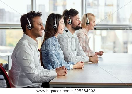 Side view happy multicultural call center operators sitting at desk. Call center workers with folded hands in bright office.