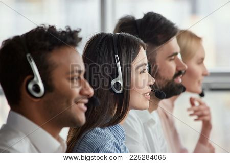 Side view asian woman with headset attentively looking. Girl in office with co-workers, profile view.