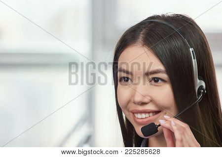 Young asian female wearing headset and talking. Pretty asian japaneese woman with headset smiling during a telephone conversation.