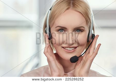 Front view mature woman's face with headset. Portrait of blond lady touching headset using both hands.