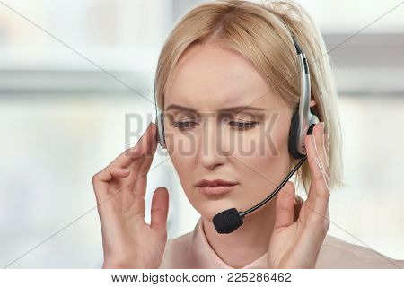 Frown face of service support call center operator. Service support client let down female blond mature call center operator.