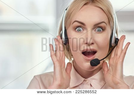 Portrait of extremely surprised woman with headset. Excited woman with headset opens mouth widely being shocked and glad, rejoices positive news.