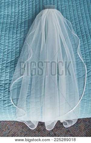 white transparent delicate bridal wedding veil with a clip made of thin delicate textile lies on a bed with a turquoise color coverlet