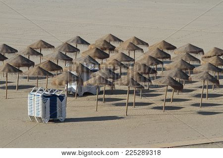 view from above of a set of umbrellas and hammocks on a empty beach