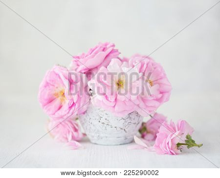 Bouquet of  pale pink roses in clay vase on light grey background. Tea roses
