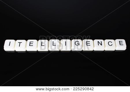 Intelligence text word title caption label cover backdrop background. Alphabet letter toy blocks on black reflective background. White alphabetical letters..