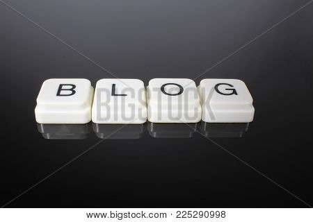 Blog text word title caption label cover backdrop background. Alphabet letter toy blocks on black reflective background. White alphabetical letters. Blog.