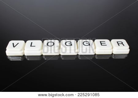 Vlogger text word title caption label cover backdrop background. Alphabet letter toy blocks on black reflective background. White alphabetical letters. vlogger,