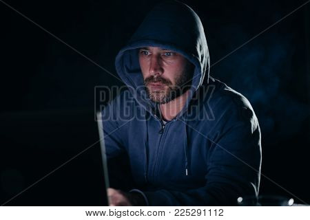 male hacker in a sweatshirt with a hood sitting at a table and looking at the laptop
