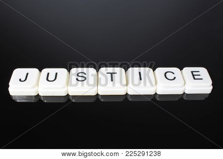 Justice text word title caption label cover backdrop background. Alphabet letter toy blocks on black reflective background. White alphabetical letters..