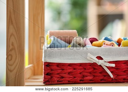 Wicker box with color sewing threads and crocheting clews on shelf