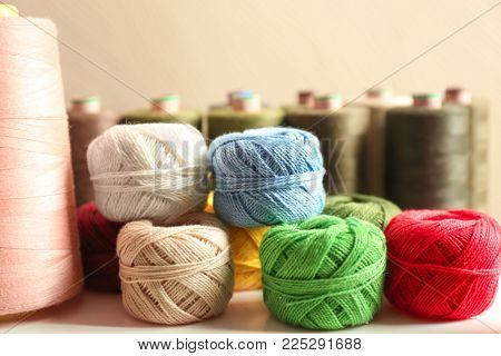 Set of color crocheting clews and sewing threads on shelf