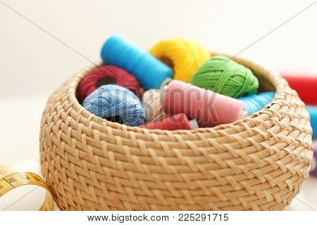 Wicker box with color sewing threads and crocheting clews on table, closeup