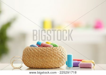 Wicker box with color sewing threads and crocheting clews on table indoors