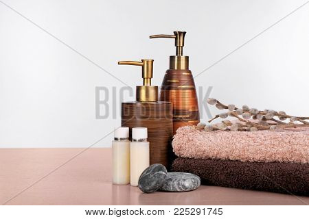 Set of fresh towels and toiletries on wooden table against white background