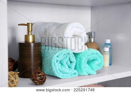 Set of fresh towels and toiletries on shelf