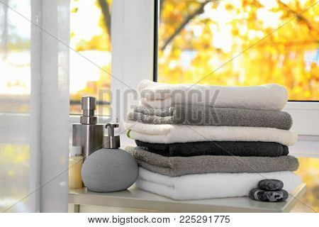 Set of fresh towels and toiletries on table near window