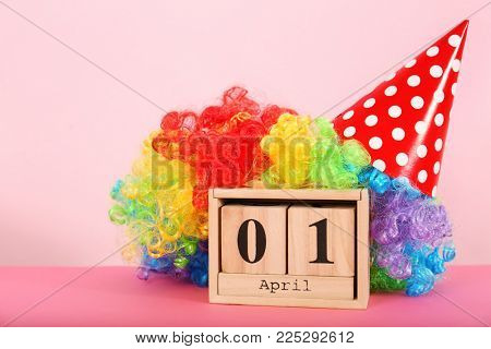 Block calendar and rainbow wig on table. April fool's day celebration