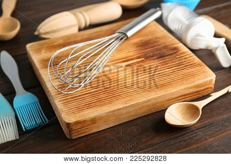 Cutting board with kitchen utensils for preparing pastries on wooden background