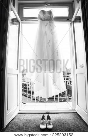 Delicate lace fabric of white long beautiful thick heavy layered luxury wedding dress of bride and shoes in daylight hang on open window empty balcony ready for marriage. Image in grayscale