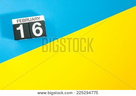 February 16th. Day 16 of february month, calendar on blue and yellow background flat lay, top view. Winter time. Empty space for text.