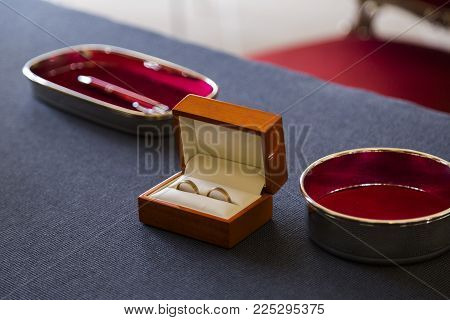 Two gold shiny wedding rings together of newly married bride and groom in beautiful brown wooden handmade small casket near metal pen on blue table