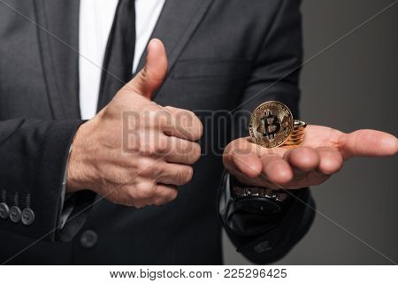 Close up of a man dressed in suit holding golden bitcoin on his palm and showing thumbs up gesture isolated over gray background