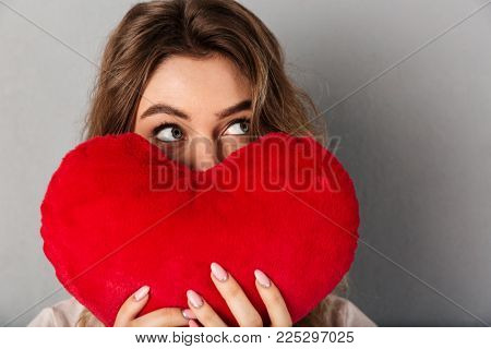 Close up image of mystery woman in t-shirt hiding behind joy heart and looking away over grey background