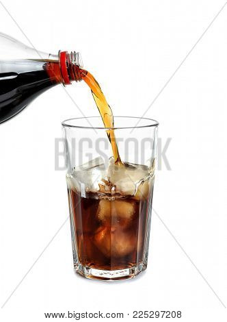 Cola pouring from bottle into glass with ice on white background
