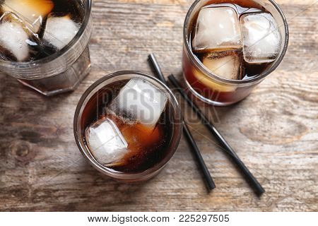 Glasses of refreshing cola with ice on wooden table
