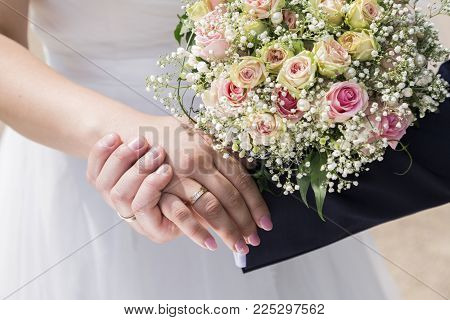 Hand of groom in a blue suit and hand of bride in white wedding dress gently holding hands with rings on fingers with beautiful wedding bouquet of pink roses.