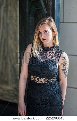 Young Woman With Tattoo Arm Waiting In Black Lace Evening Gown In Doorway.  Shot At Ventura City Hal