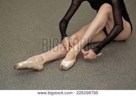 The ballerina ties the tapes with pointe shoes. Slender long female legs. Beautiful graceful hands. Shooting close-ups