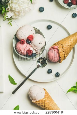 Flat-lay of Pink strawberry and coconut ice cream scoops in bowl, sweet cones, peony flowers bouquet and fresh berries over white background, top view. Summer food concept