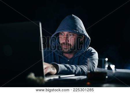 male hacker in a sweatshirt with a hood sitting and looking at the laptop