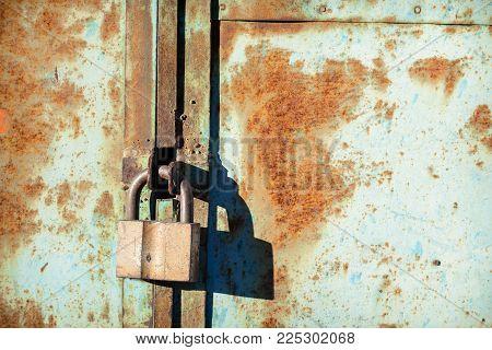 old iron barn castle on a metal rusty door in hard sunlight.  Access is denied
