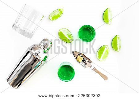 Make cocktail with absinthe. Shaker, shots, lime slices on white background top view, poster