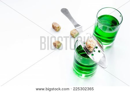 Traditions of drinking absinthe. Special spoon and sugar cubes near shots on white background top view. poster