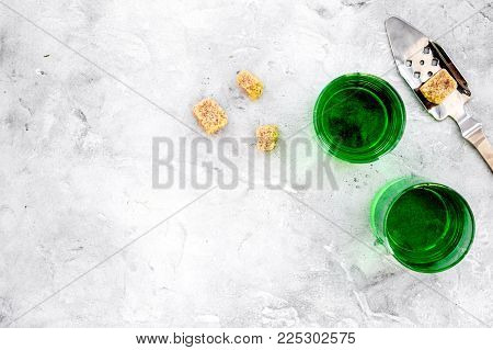 Traditions of drinking absinthe. Special spoon and sugar cubes near shots on grey background top view. poster