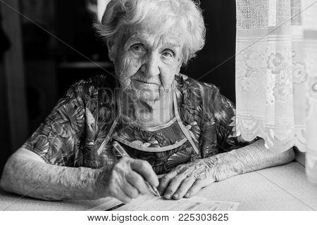 Elderly woman fills in receipts for utilities.