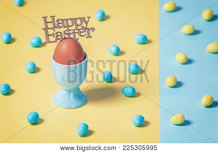 Minimalistic Easter composition with boiled egg in cup on plain yellow and blue background with seeg sweets spread arround.
