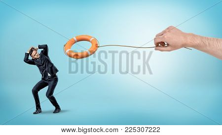 A small businessman hiding from an orange life buoy thrown down by a giant male hand. Forced saving. Crisis management. Outside help.