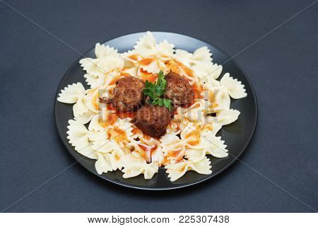 Meat Balls and Farfalle Pasta on Black plate