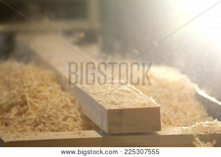 Process of sawing a board with a chain saw, a lot of sawdust, industrial concept