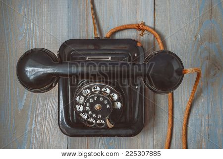 An old black telephone set with a cloth cord and a round dial is on a painted table.View from above.