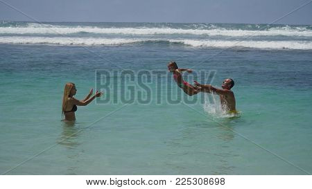 Happy family with daughter having fun on the sea during summer vacation. Couple with a child playing with her daughter in the azure waters of the ocean. Travel concept. Family relationships. Bali.