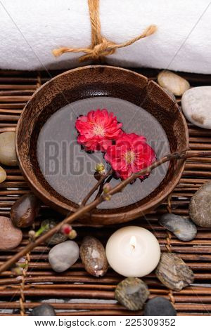 Spa setting with red cherry ,stones ,candle ,towel, bowl on mat