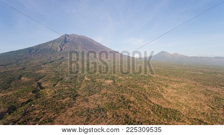 Aerial view of Volcano Mount Agung with smoke billowing out at sunrise, Bali, Indonesia. Conical volcano of Gunung Agung. Rural mountain landscape.
