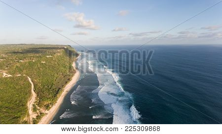 Aerial view of tropical beach with large wave. Large waves of turquoise water crushing on a beach Melasti, Bali, Indonesia. Travel concept.