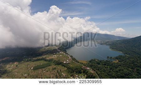 Aerial view of Lake Tamblingan, a caldera lake at Bali. Beautiful lake with turquoise water in the mountains of the island of Bali. Landscape, lake among mountains, sky, clouds.